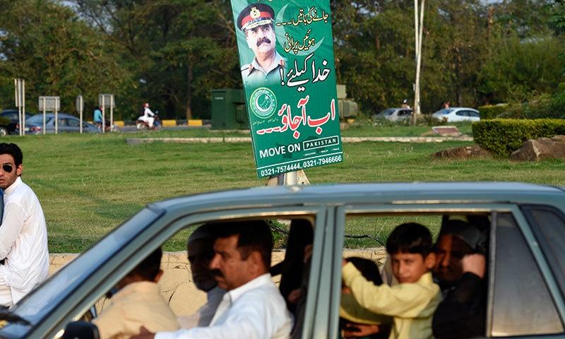 اسلام آباد میں شہری آرمی چیف جنرل راحیل شریف کے پوسٹر کے قریب سے گزر رہے ہیں—۔فوٹو/ تنویر شہزاد/ وائٹ اسٹار