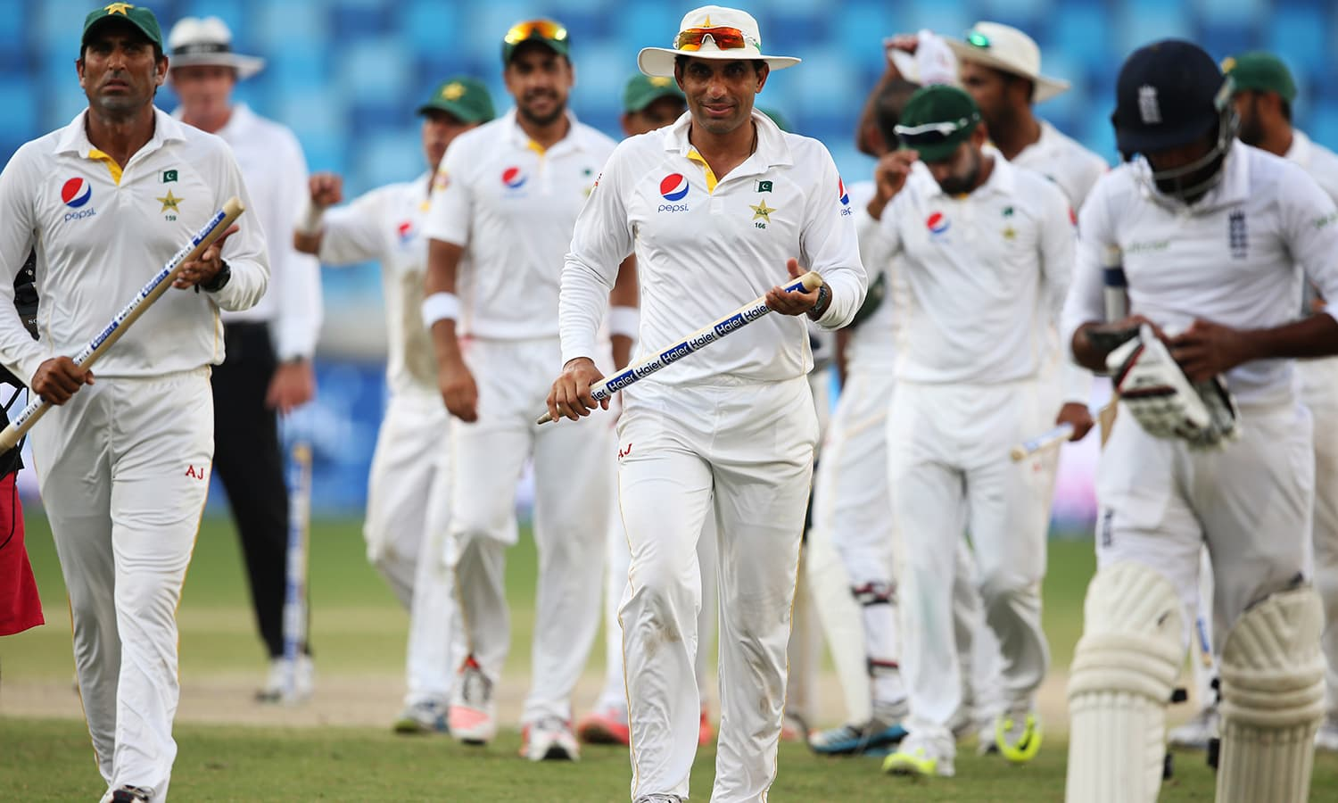 Younis Khan and Misbah-ul-Haq walk with stumps as they leave the green. — AP