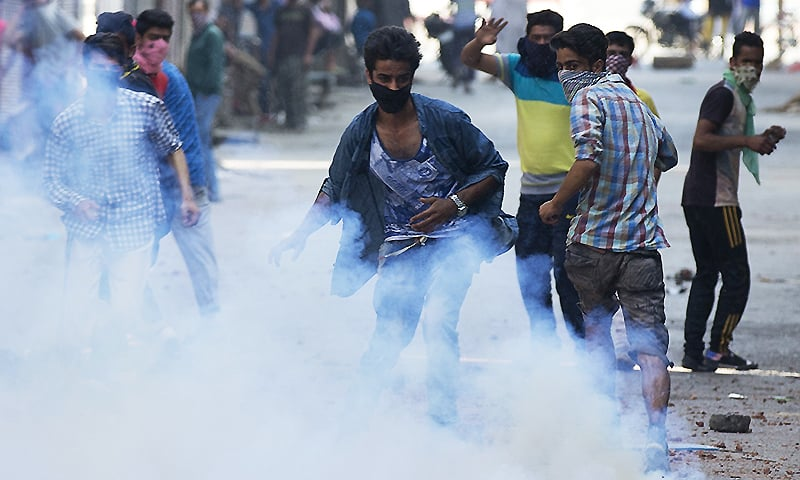 Protesters reacting to the killing of Burhan Wani are engulfed in tear gas smoke as they clash with Indian policemen in Srinagar. ─ AP
