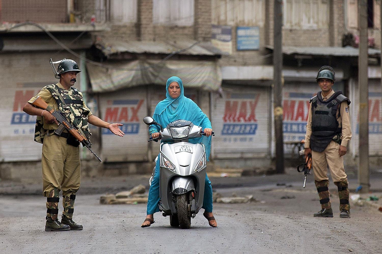سری نگر میں کرفیو کے دوران ہندوستانی افواج نے ایک خاتون کشمیری کو روکا ہوا ہے — اے پی