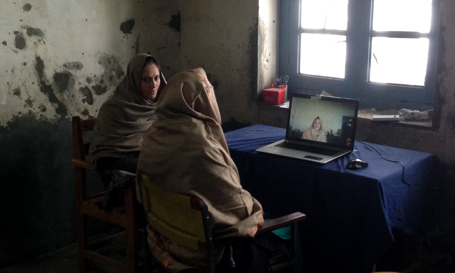 A woman and a community Mental Health Worker sit by a laptop during a telespsychiatry session in Charun Oveer.