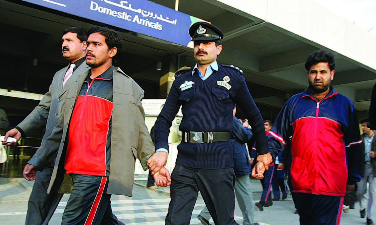 Islamabad airport security escorts Pakistani deportees in 2007 | AFP