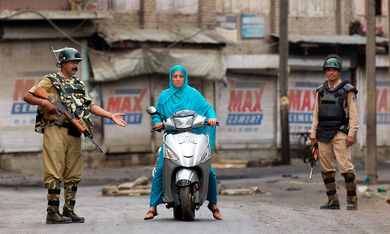Indian paramilitary soldiers stop a Kashmiri woman during curfew in Srinagar. —AP