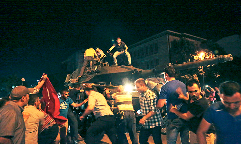 Turkish people attempt to stop a tank moving into position in Ankara, Turkey, late Friday, July 15, 2016. — AP