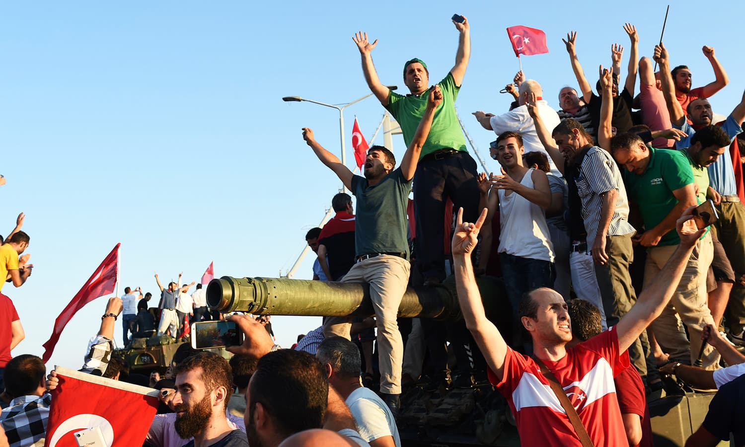 People rally on a tank after they take over military position on the Bosphorus bridge in Istanbul on July 16. � AFP