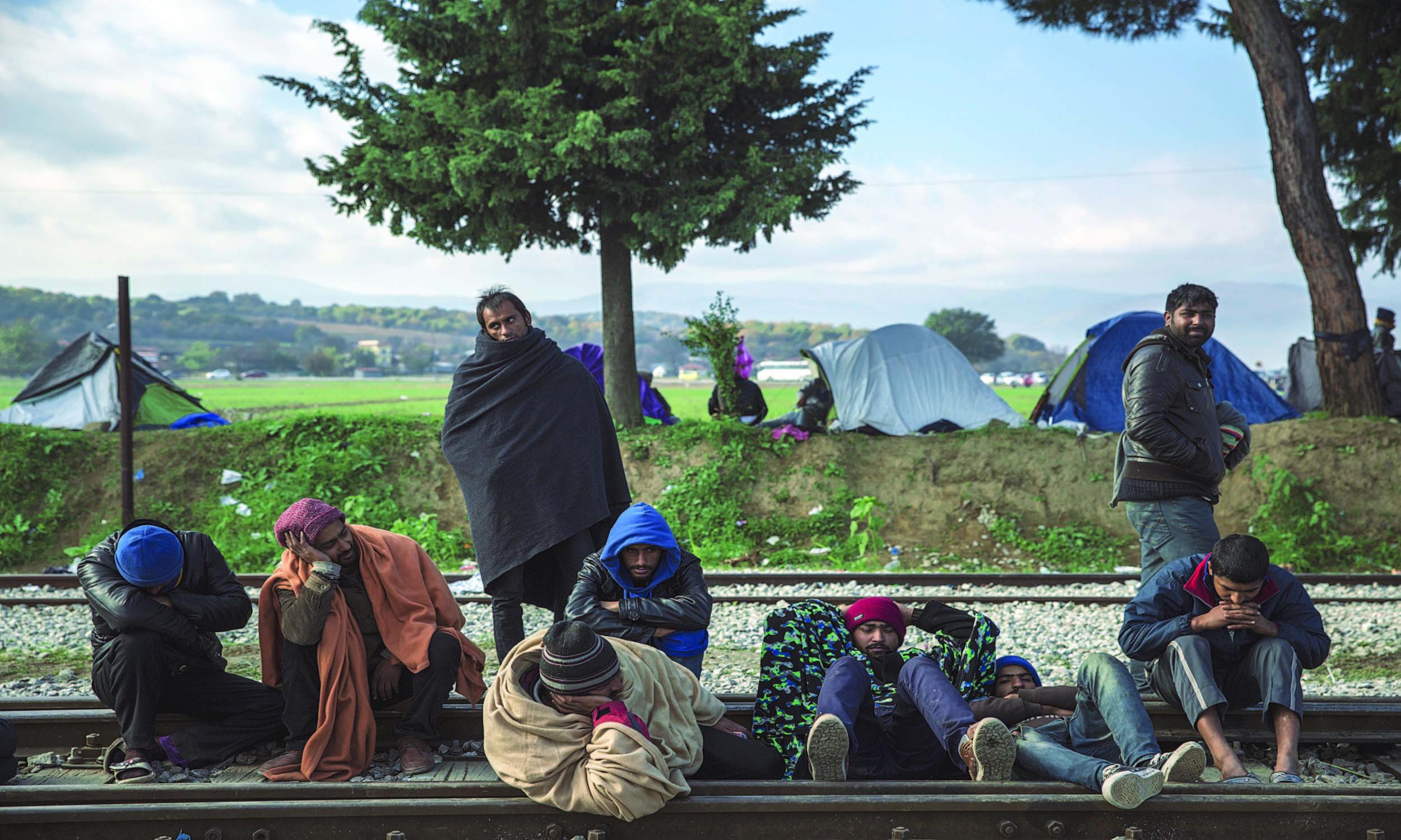 Pakistani migrants stranded in Greece sleep on the train tracks at Idomeni, an informal camp on the Macedonian border | Jodi Hilton