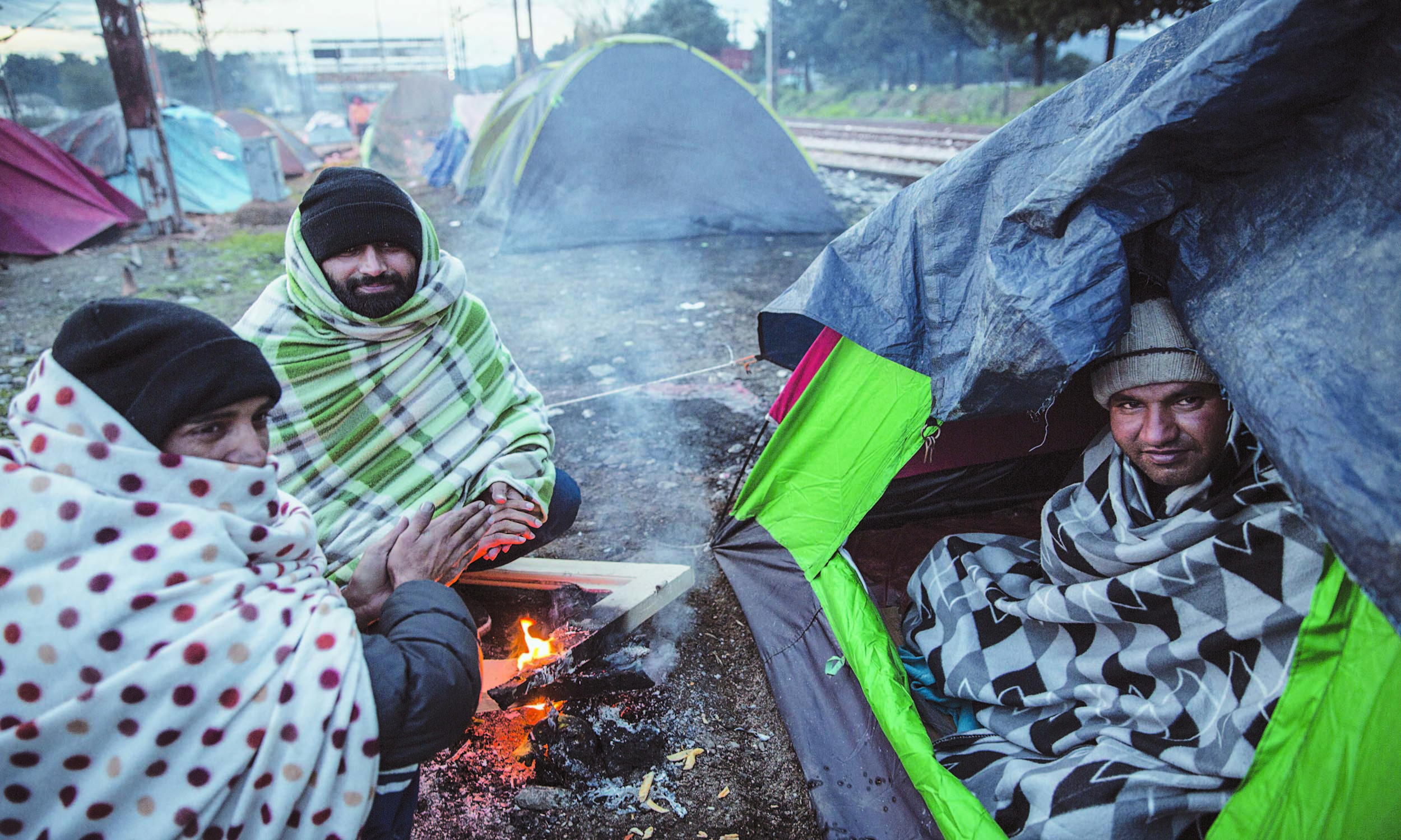 Pakistani migrants sit around a fire at Idomeni camp on a cold morning in November 2015 | Jodi Hilton