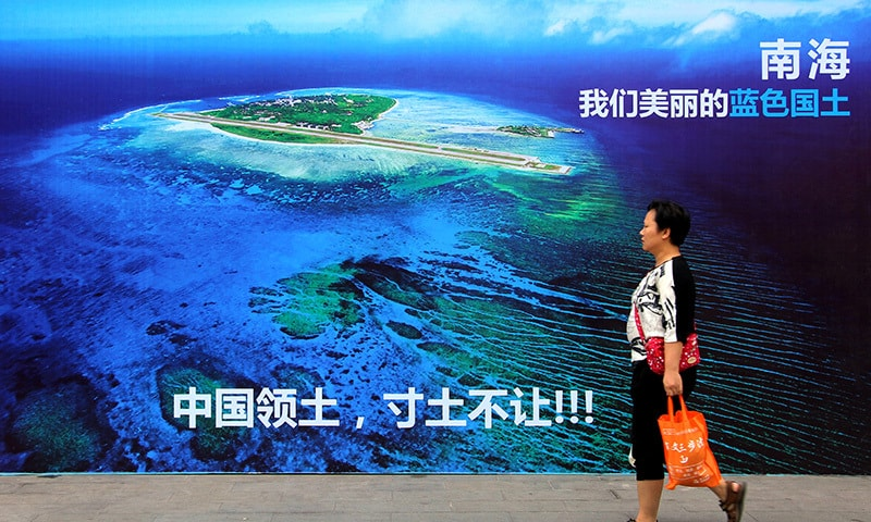 "A woman walks past a billboard featuring an image of an island in South China Sea on display with Chinese words that read: ""South China Sea, our beautiful motherland, we won't let go an inch"" in Weifang in east China's Shandong province.  —AP"