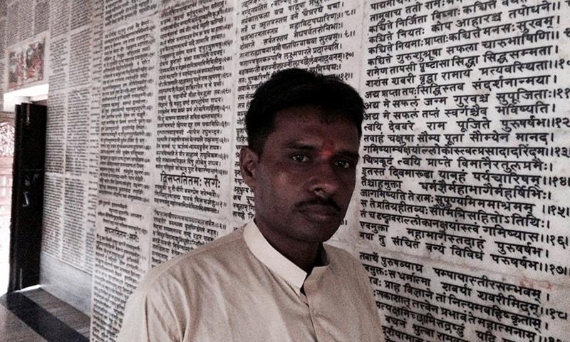 وشوا ہندو پرشاد کے ترجمان شرد شرما ایک مندر میں موجود ہیں جس کی دیوار پر رامائن لکھی ہے—فوٹو/ رائٹرز