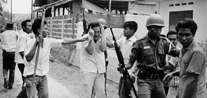 Soldiers and members of pro-military religious groups beat up an alleged communist at a university in Jakarta, Indonesia, during the 1965 coup.