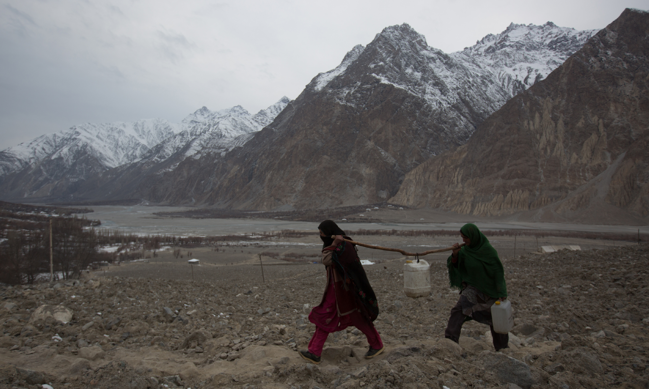 Women carry water canisters, after a flash flood destroyed their homes in Brep, a village in Chitral | Danial Shah