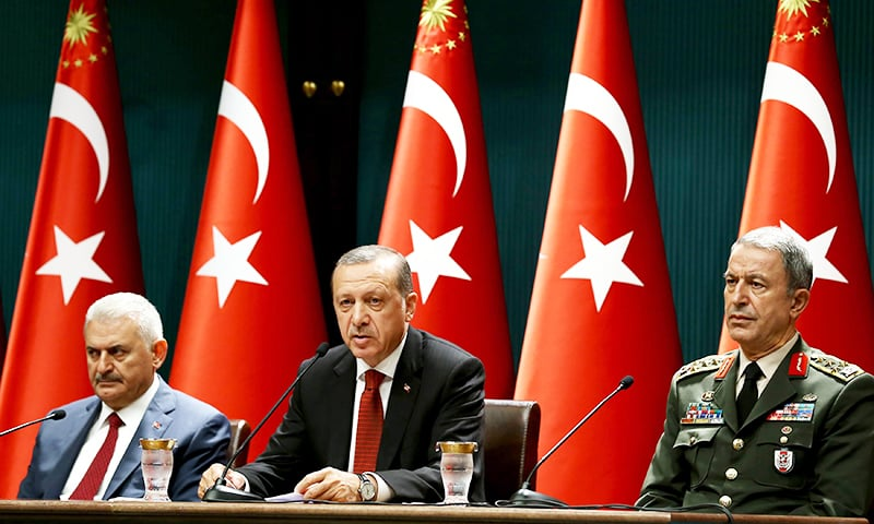 A handout photo released by the Turkish Presidential Press Office shows Turkish President Recep Tayyip Erdogan (C) delivering a speech during a press conference at the Presidential Complex in Ankara on July 22, 2016, flanked by Turkish Prime Minister Binali Yildirim (L) and Chief of the General Staff of Turkey, Hulusi Akar. ─ AFP