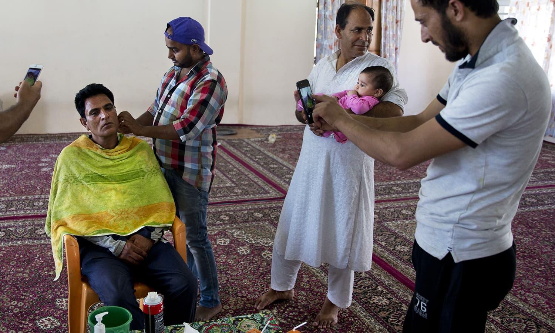 Kashmiris perform traditional hair cut to the groom Shiekh Naseer Ahmed during his wedding ceremony in Srinagar.— AP