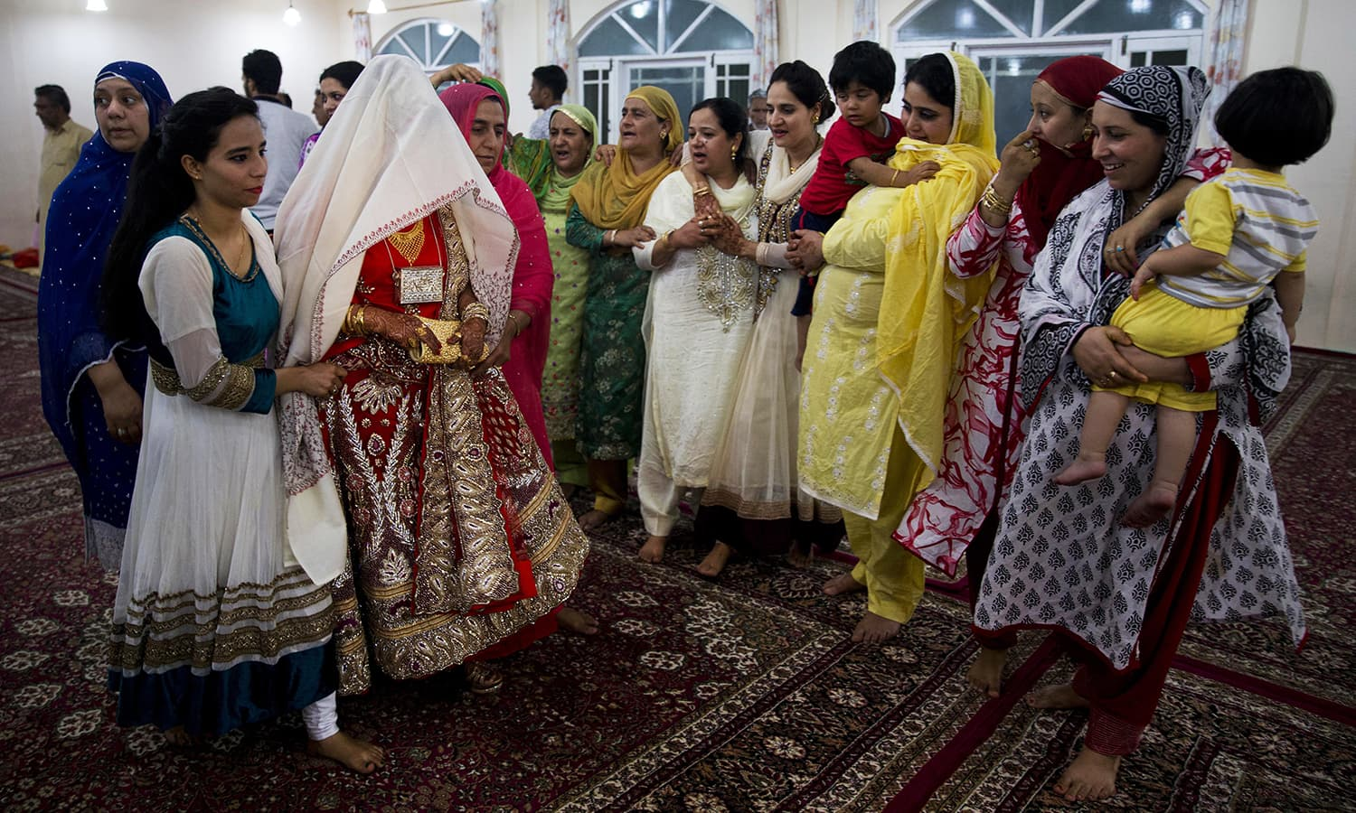 Relatives of the groom surround Kashmiri bride Quansar, covered with a white shawl, during her wedding ceremony.— AP