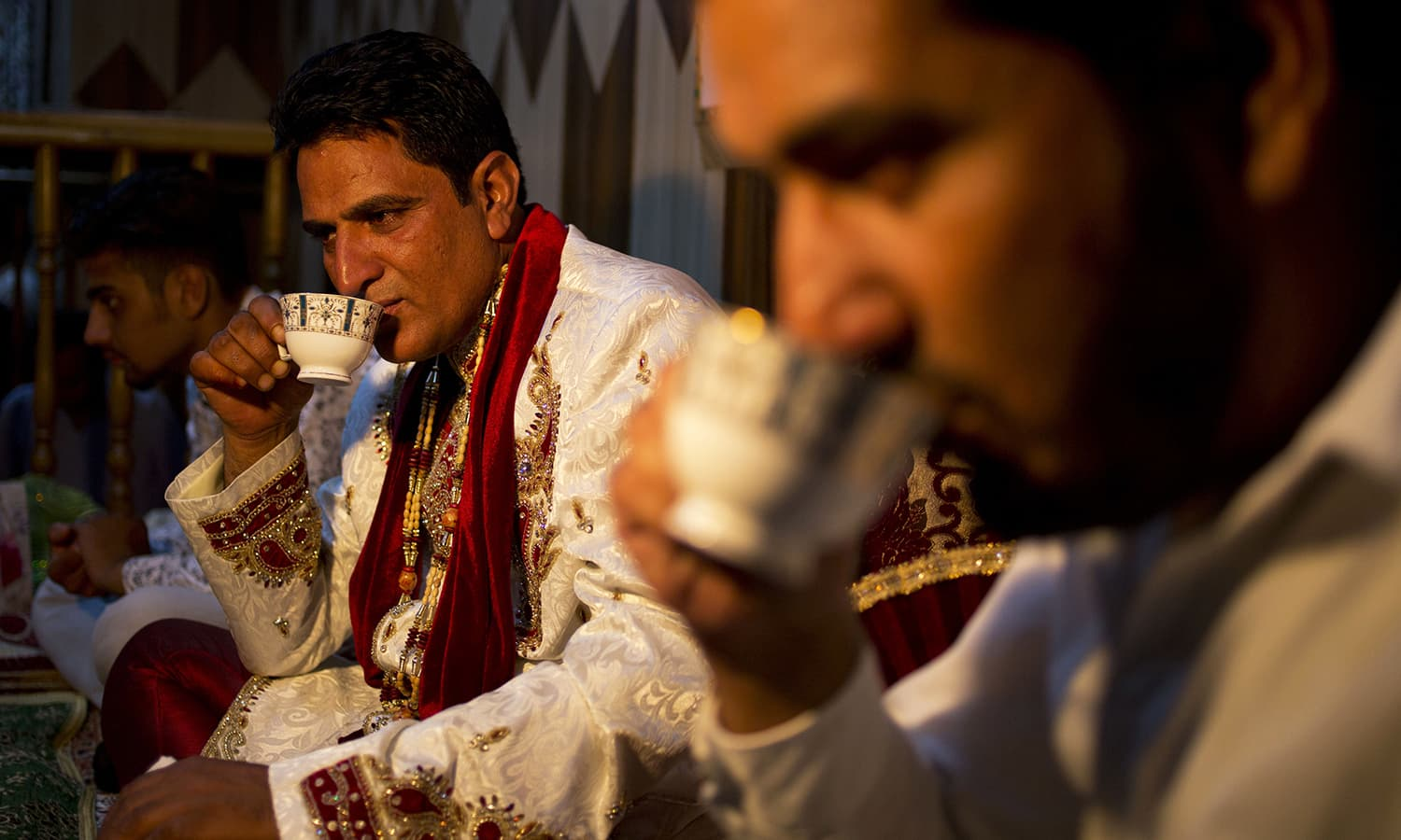 Groom Sheikh Naseer Ahmed, center, sips tea during his marriage ceremony at the bride house in Srinagar.— AP