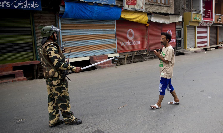 An Indian Paramilitary soldier stops a Kashmiri Muslim man in Srinagar, July 22.— AP