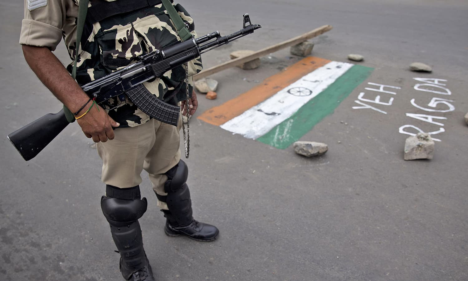 """An Indian Paramilitary soldier stands guard near the graffiti that reads: """"trample"""" on the Indian flag in Srinagar, July 22.— AP"""