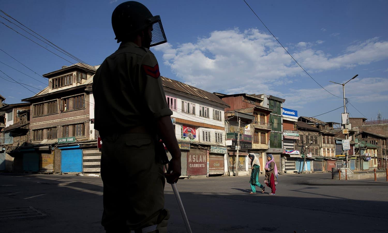Kashmiri women walk on a deserted street, past an Indian policeman during curfew in Srinagar.— AP