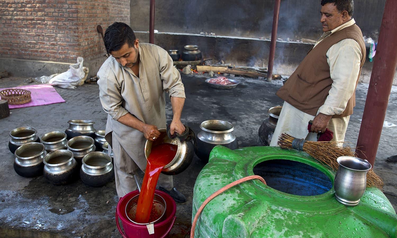 Mohammed Munnawar, right, and Muneer Ahmed, Kashmiri wazas, or chefs, cook for a wedding feast in Srinagar.— AP