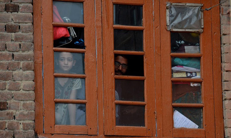 ایک کشمیری لڑکی اپنے گھر کی ایک کھڑکی سے باہر جھانک رہی ہے — اے ایف پی