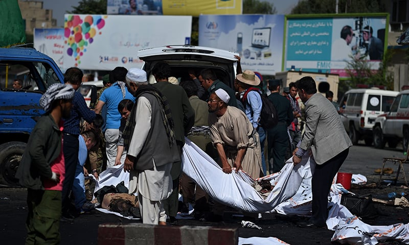 Afghan volunteers carry the bodies of victims at the scene of the suicide attack. —AFP