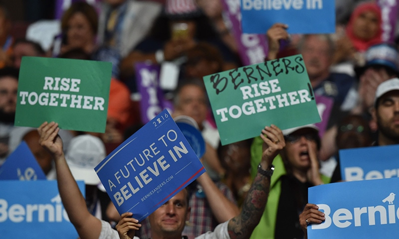 People holds signs during the 2016 Democratic National Convention.— AFP