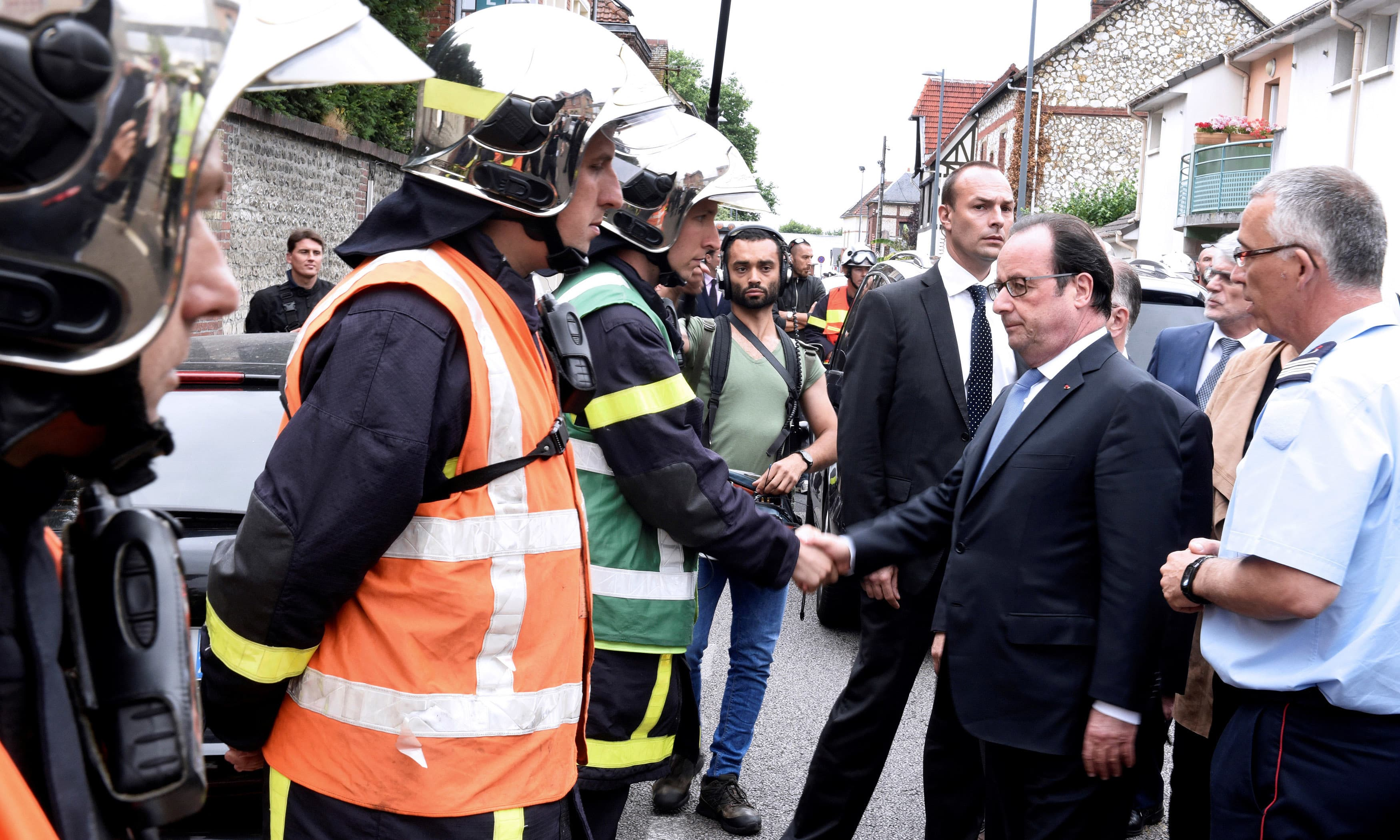 French President Francois Hollande shakes hands with firemen as he arrives after a hostage-taking at a church in Saint-Etienne-du-Rouvray. ─Reuters