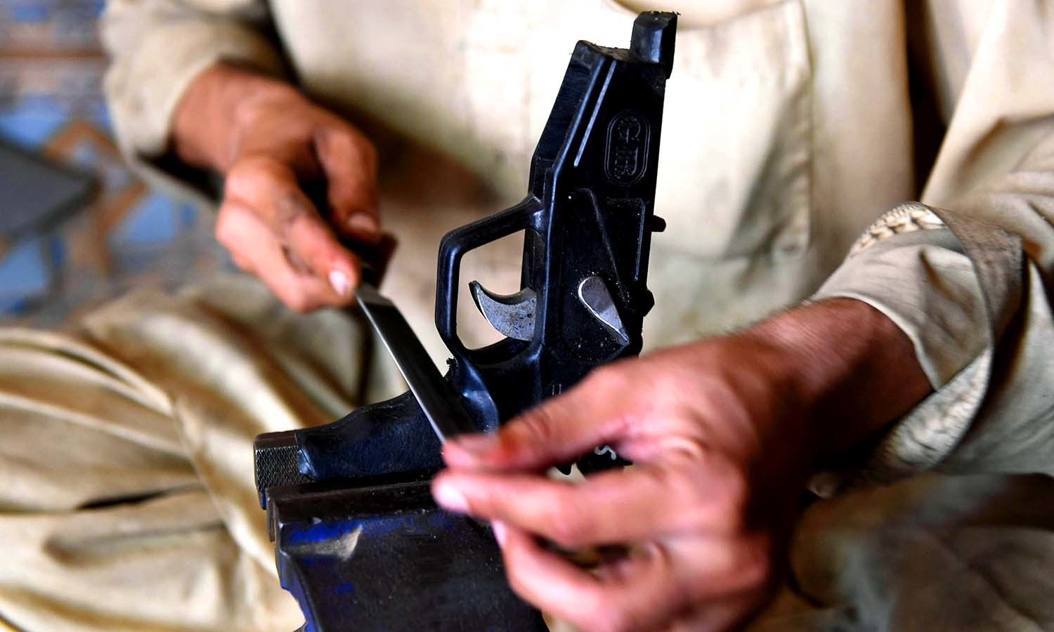A gunsmith makes a pistol at a small workshop in Darra Adamkhel. ─AFP