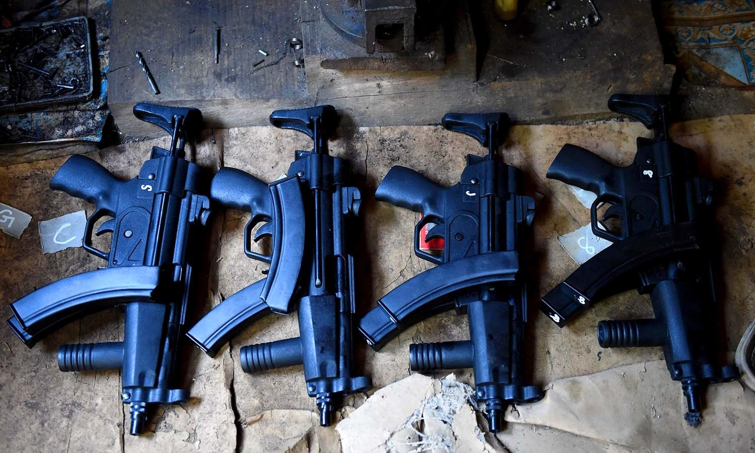 Replicas of Turkish and Bulgarian made MP5 submachine guns are seen at a workshop. ─AFP