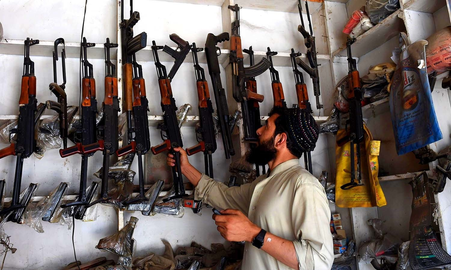 An arms seller picks an assault rifle from a shelf at his shop. ─AFP