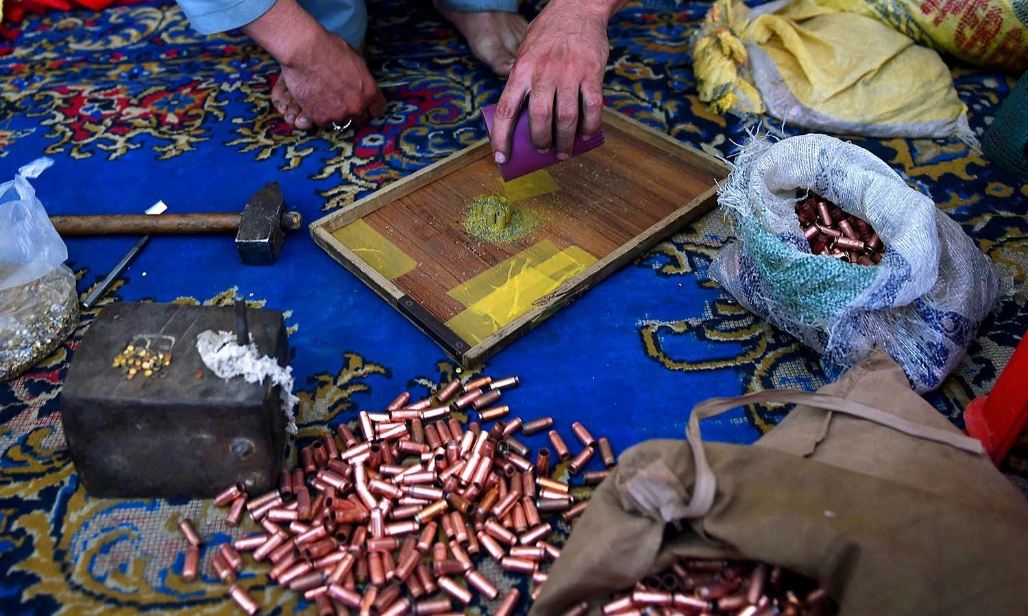 Gunsmiths assemble bullets. ─AFP