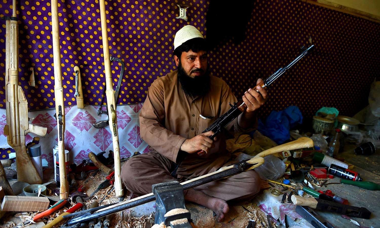 A gunsmith holds an assault rifle. ─AFP