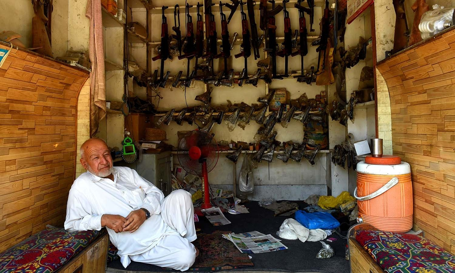 An arms seller waits for customers at his shop. ─AFP