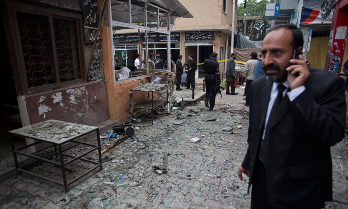 A lawyer talks on his mobile phone at the site of a bomb attack in a court complex in Islamabad  | AP