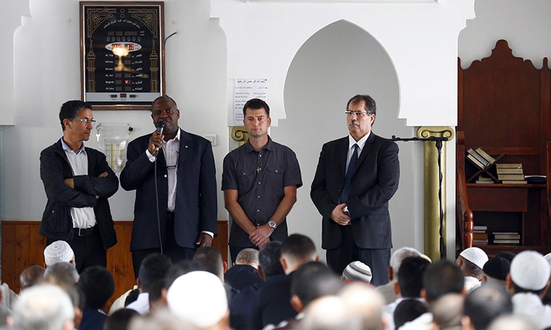 Saint-Etienne-du-Rouvray's Priest Auguste Moanda, second left, delivers his speech , flancked by Mohammed Karabila, President of the Muslim Regional Council of Normandy, left, Priest Pierre, center and Anouar Kbibech, President of the French Council of the Muslim Faith, right, as muslim worshippers attend the friday prayer at the Yahya Mosque, in Saint-Etienne-du-Rouvray, Normandy.─ AP