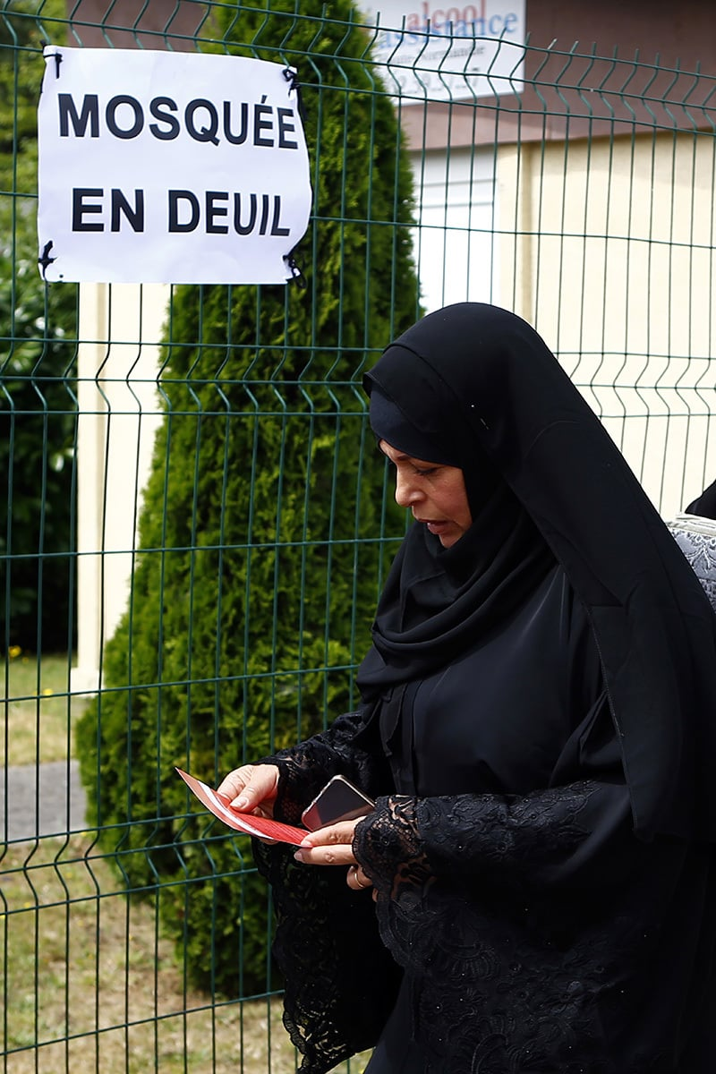 """Muslim worshipper walks past a poster reading """"Mourning Mosque"""" after the friday prayer at the Yahya Mosque, in Saint-Etienne-du-Rouvray, Normandy, France.─AP"""