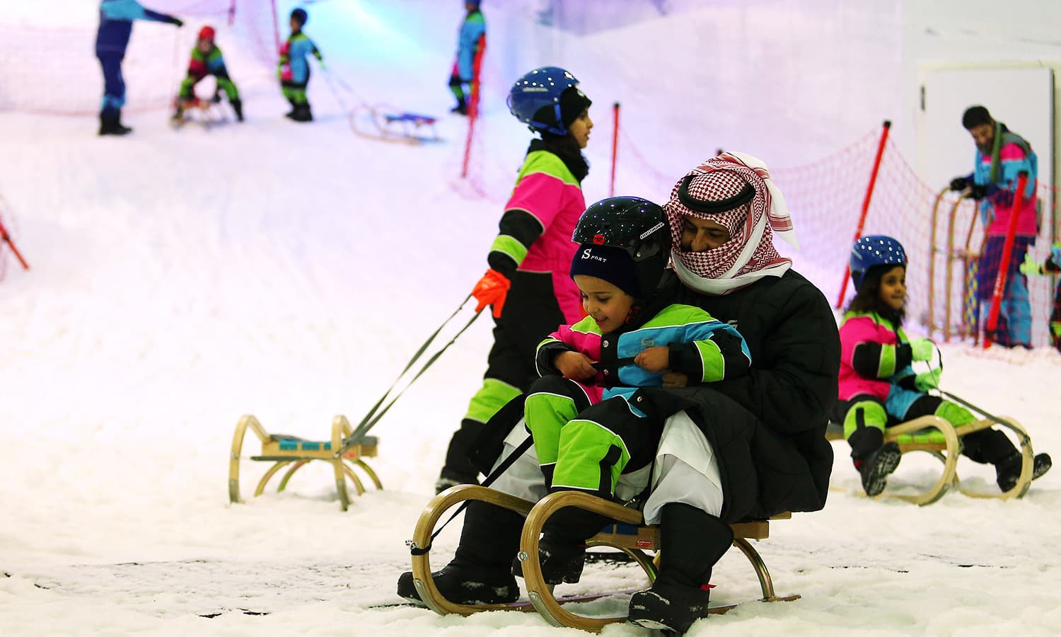 """This file photo taken on July 20, 2016 shows a Saudi man and a boy sliding on a sledge at the indoor snow theme park """"Snow City"""" in the Al-Othaim Mall Rabwa in the capital Riyadh. ─ AFP"""