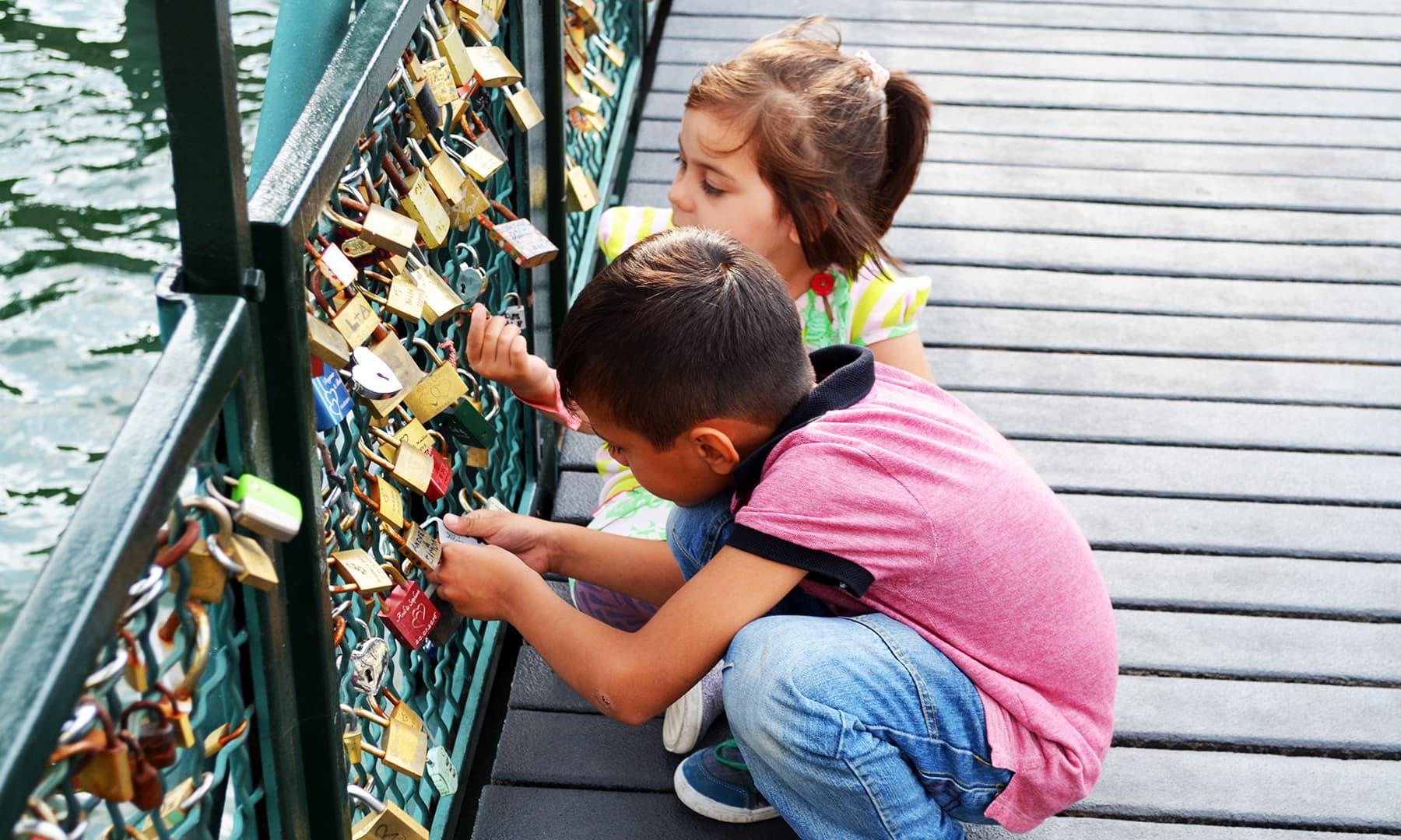 پل پر بچے تالوں کو دیکھ رہے ہیں —فوٹو رمضان رفیق