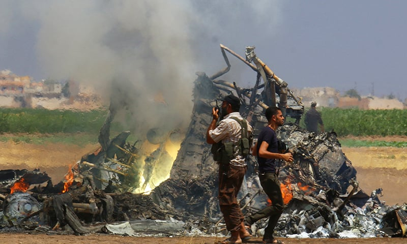 Militants inspect the wreckage of a Russian helicopter that had been shot down in the north of Syria's rebel-held Idlib province. -Reuters