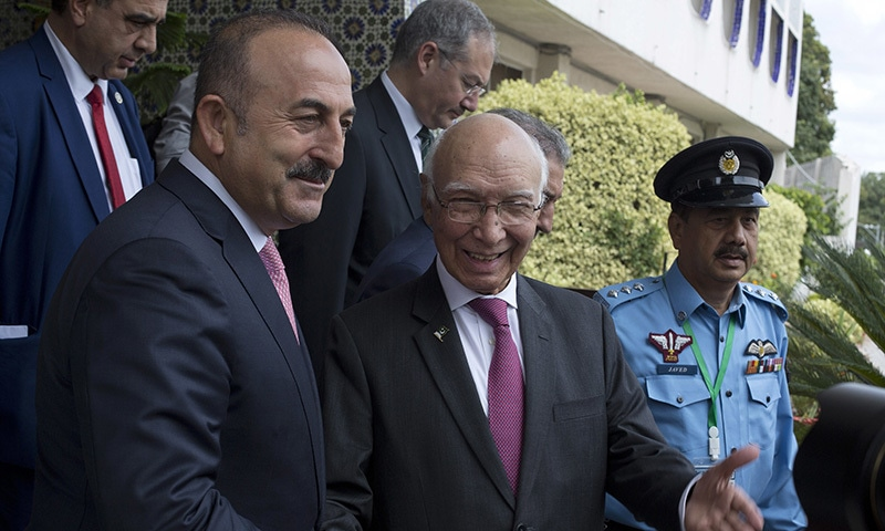 Special Adviser to the PM on Foreign Affairs Sartaj Aziz shakes hands with Turkish Foreign Minister Mevlut Cavusoglu, at the foreign ministry in Islamabad. ─ AP
