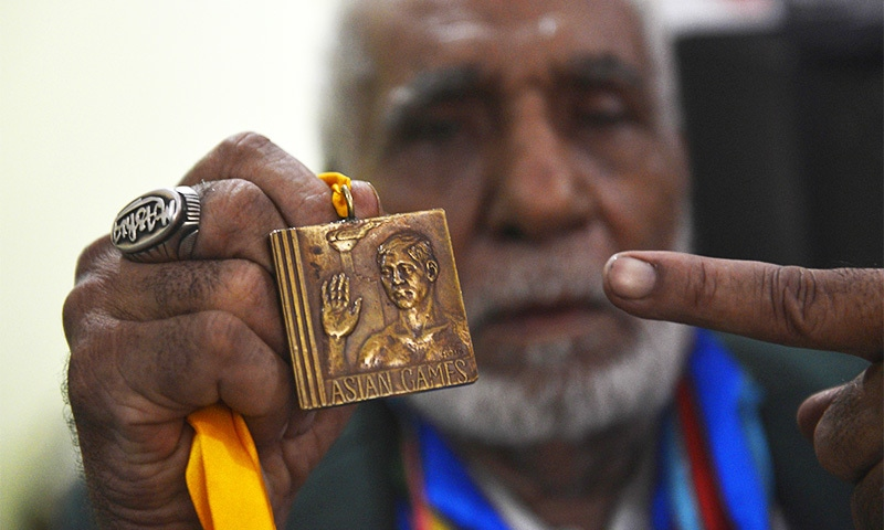 Former Olympian Muhammad Ashiq holds his medals as he posses at his residence in Lahore.—AFP