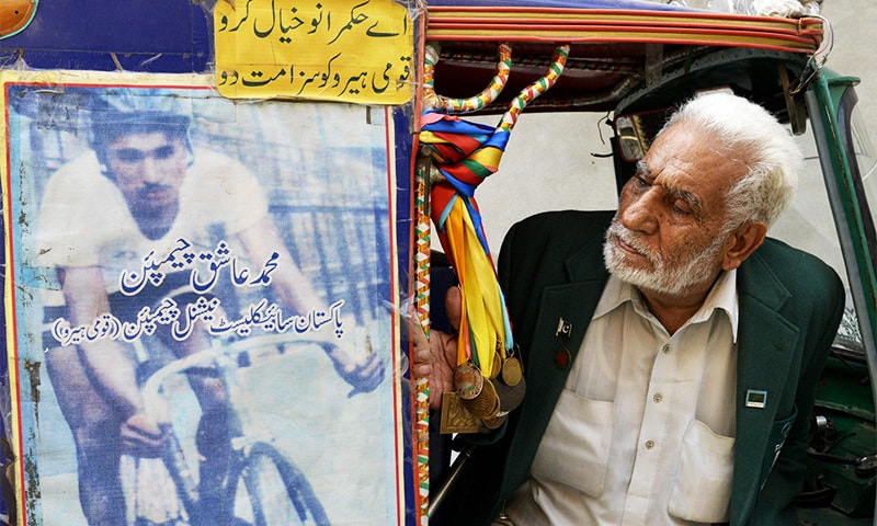 Former Pakistani Olympian Muhammad Ashiq waiting for passengers in his rickshaw in Lahore.—AFP
