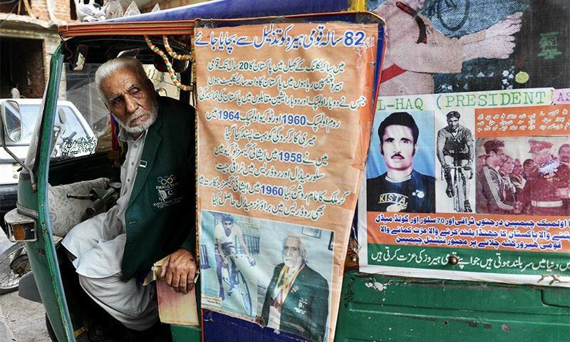 Former Olympian Muhammad Ashiq poses in his rickshaw in Lahore.—AFP