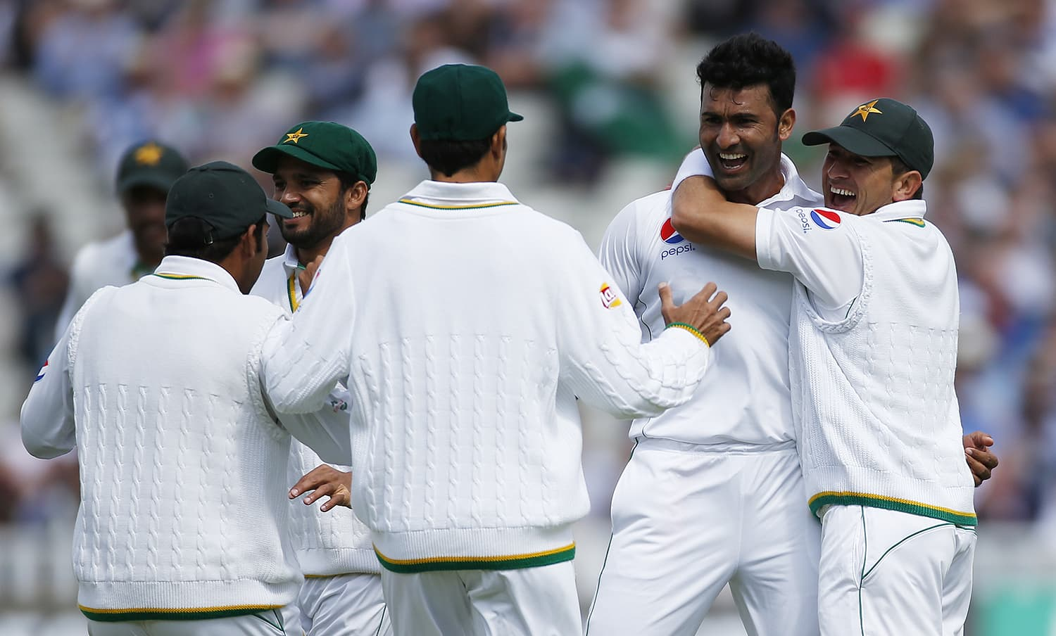 Sohail Khan celebrates with team mates after taking the wicket of England's Joe Root. — Reuters