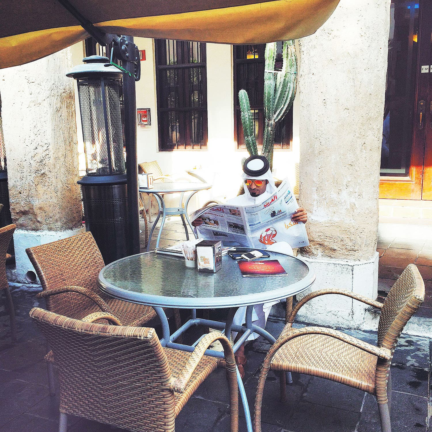 A local man reading the newspaper at a café in Souq Waqif.