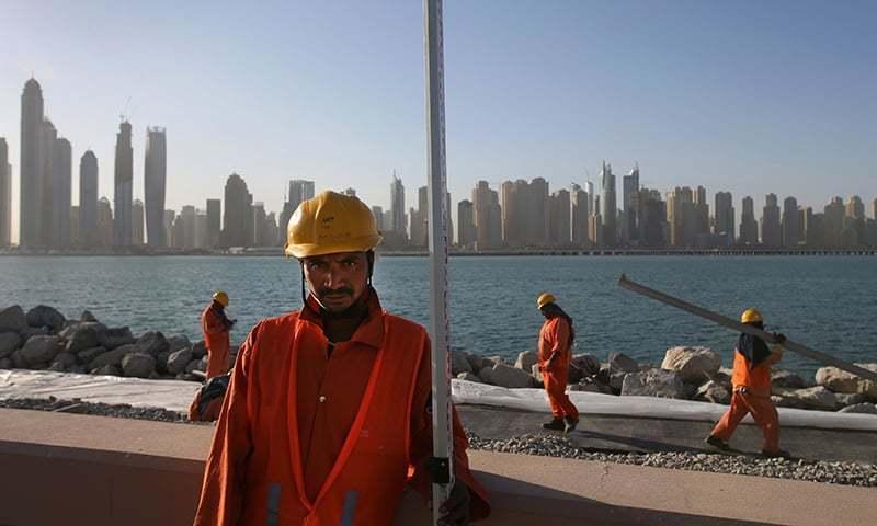 غیر ملکی مزدور دبئی میں پام جمیرہ کی سائٹ پر تعمیراتی کام میں مصروف ہیں۔ — اے پی/فائل۔