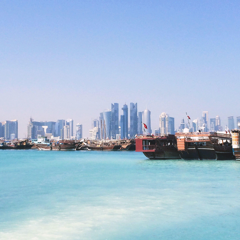 Qatar's capital Doha and traditional boats docked within the Doha Bay.