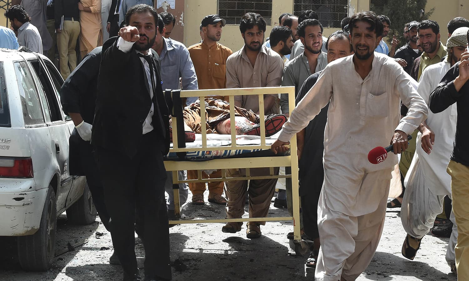 Lawyers and local media personnel carry a bed to move the body of a news cameraman after a bomb explosion at a government hospital premises in Quetta on August 8, 2016.—AFP