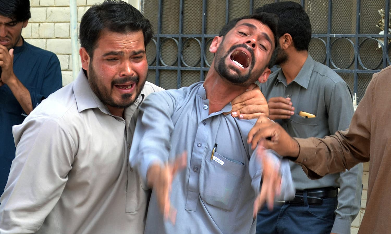 Bystanders react at the site after a bomb explosion at a government hospital premises in Quetta on August 8, 2016.—AFP