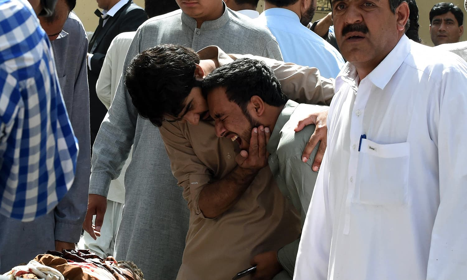 Local journalists react over the body of a news cameraman after a bomb explosion at a government hospital premises in Quetta on August 8, 2016.—AFP